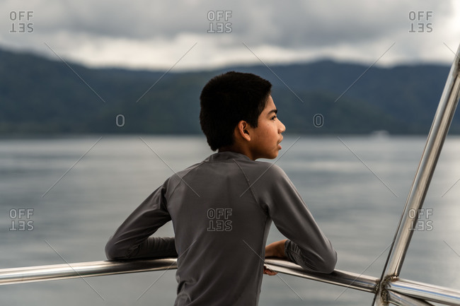 Young boy looking out from railing of a boat