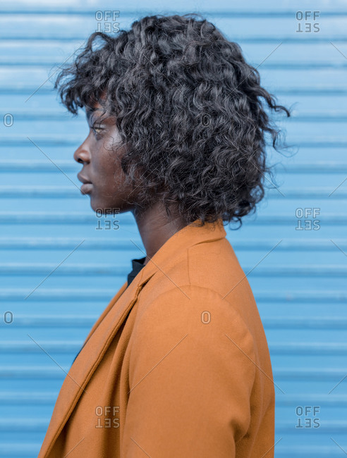 Profile view of a young African American woman standing in front of blue wall