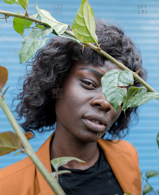 Young African American woman standing in front of blue wall looking through vines