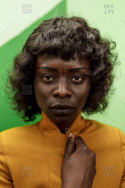 Close up of a young African American woman standing in front of a green wall
