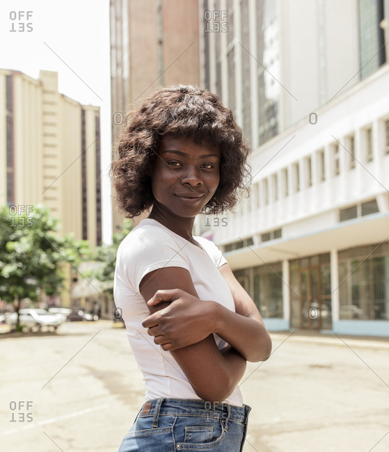 Young African American woman standing on sunny city street