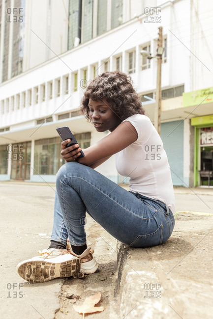Young African American woman sitting on city street side using cell phone