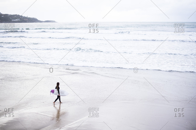 Woman Surfing on a stormy day at Hendaye Plage on the border of France