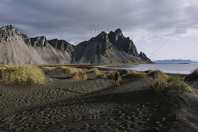 Young man looking at dramatic mountains on beach in Iceland