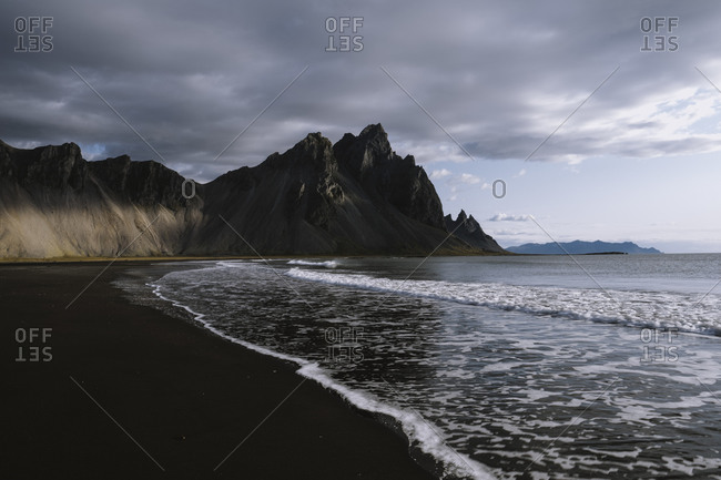 Sunrise on dramatic beach in Iceland surrounded by mountains