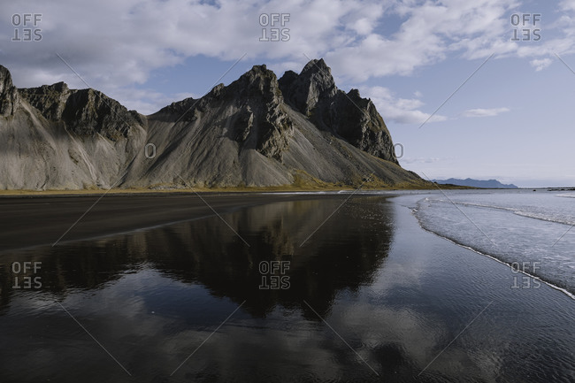 Dramatic blue sky and mountain reflection on beach in Iceland