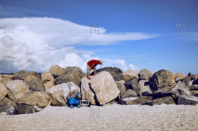 Local fisherman climbing on jetty with fishing equipment on sand