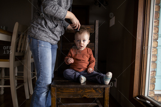 Toddler boy getting haircut at home by mom