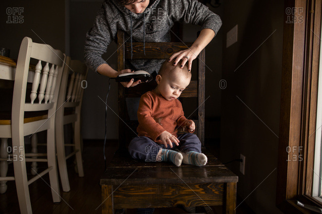 Young boy getting a home haircut by mom