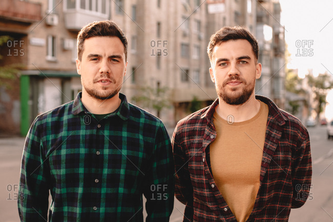 Portrait of adult twin brothers standing in city street in summer