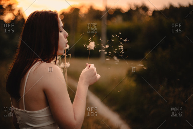 Young woman blowing dandelion while standing on meadow in summer