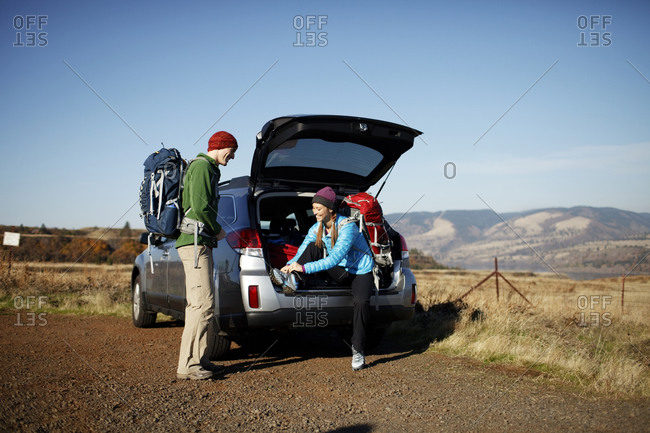 Man and woman by car getting ready for hike at trailhead