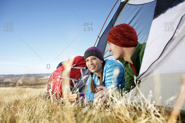 Male and Female backpackers hanging out in tent in grassy field