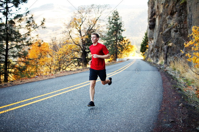 Male runner in his mid 20s running along scenic road in Rowena