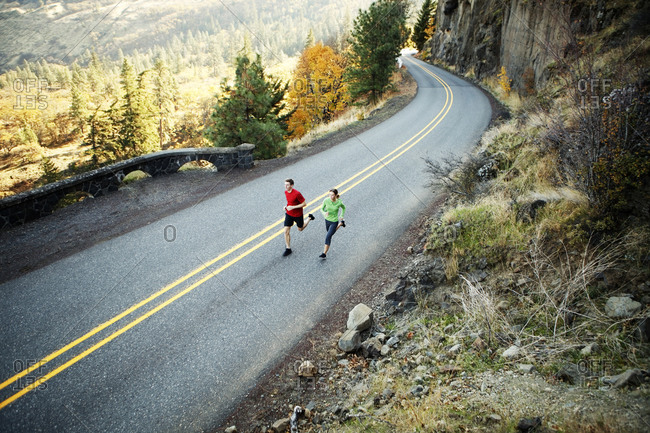 Two runners in their mid 20s running along scenic road in Rowena