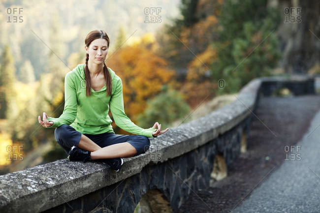 Woman meditating on rock wall on side of the road