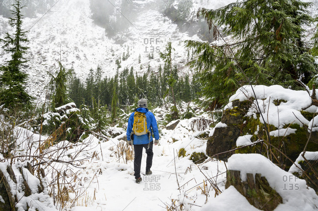 Hiker on snowy trail in the cascade mountains