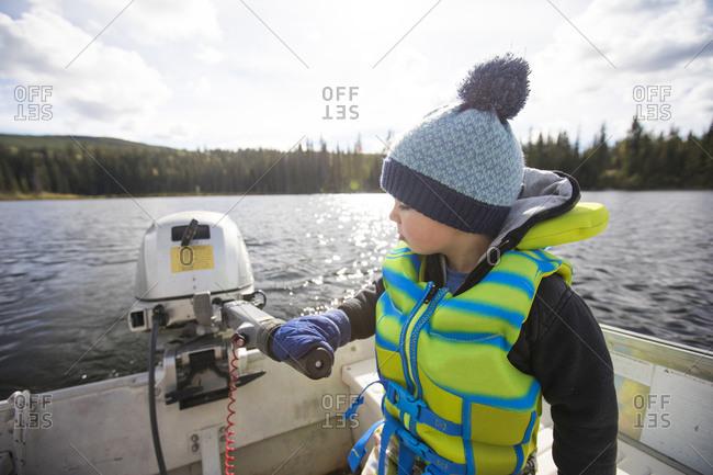 Toddler boy driving motorboat on lake.