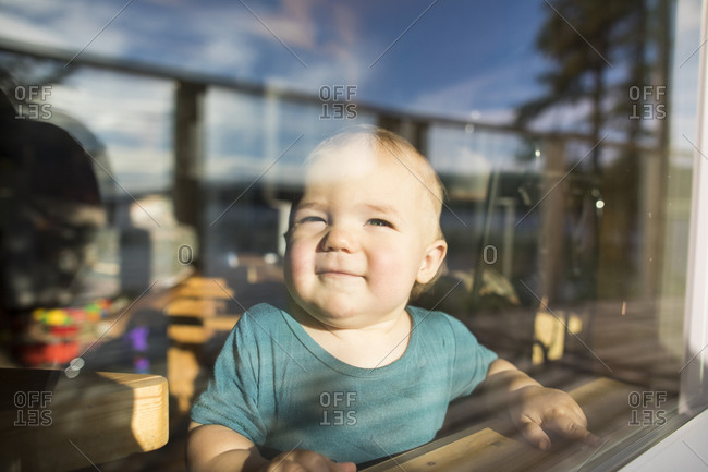 Portrait of young girl looking out through cabin window.