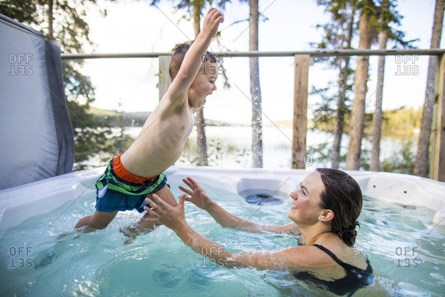young boy jumping to mother in hot tub during vacation.