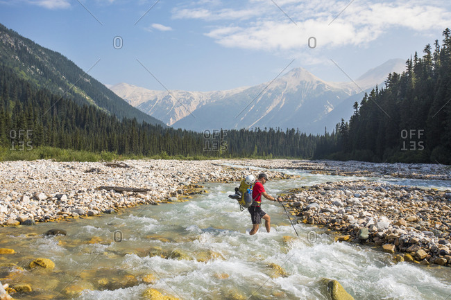 Backpacker crosses icy river in British Columbia, Canada.