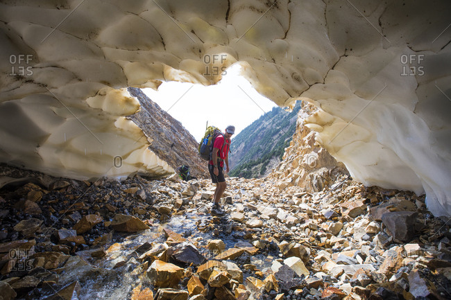 Backpacker approaches entrance to snow tunnel