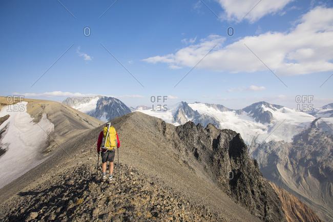 Rear view of backpacker hiking on rocky summit ridge.