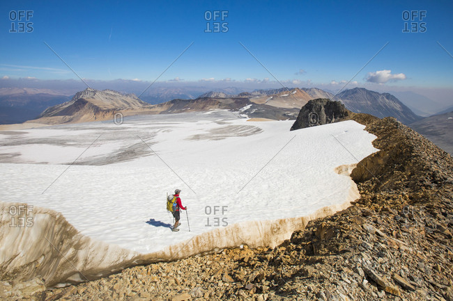 high angle of backpacker hiking across tip of huge glacier.