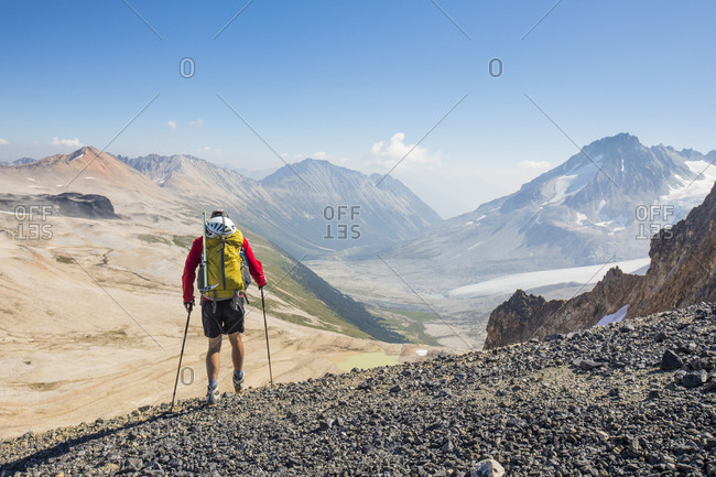 Rear view of male backpacker in high mountains.