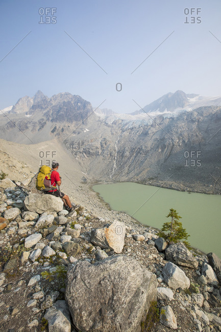 Hiker takes a break with view, Athelney Pass, British Columbia, Canada