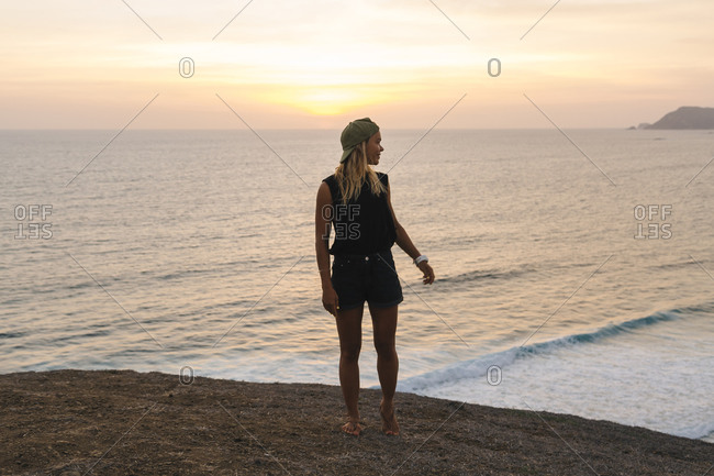 Young woman standing on rock at the beach at sunset