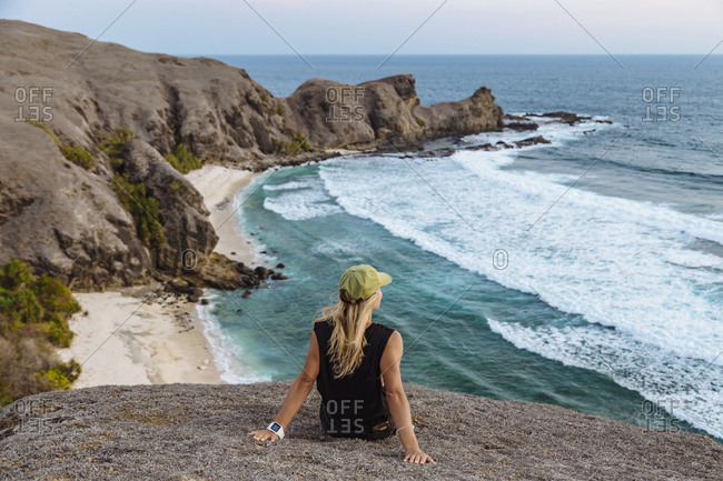 Young woman sitting on rock at sunset