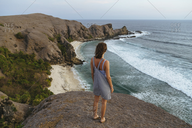 Young woman staying at hill and looking at view