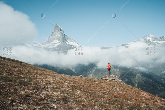 Yong woman standing on rock in front of Matterhorn above clouds