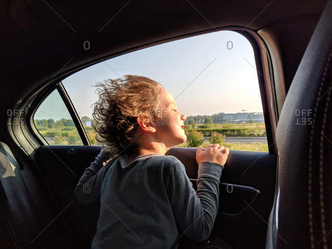 Little boy enjoying the wind in his hair while in the car