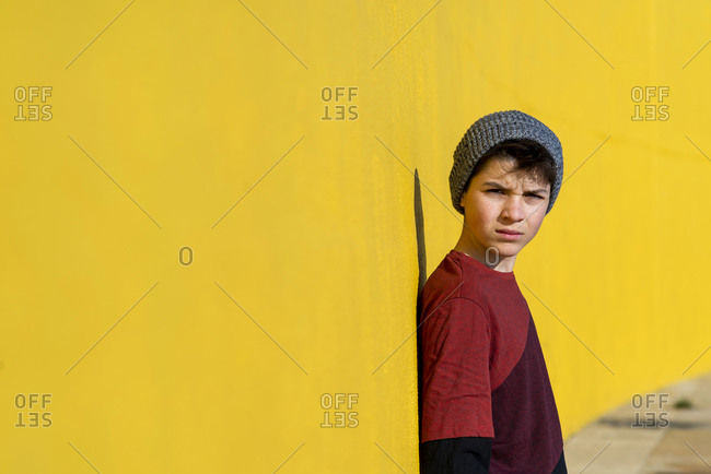 Teen with wool cap leaning against a yellow wall while looking camera