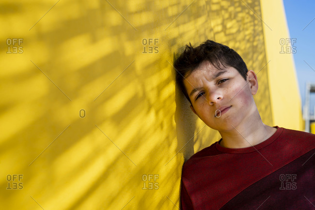 Portrait of cheerful teen leaning on yellow wall while looking camera