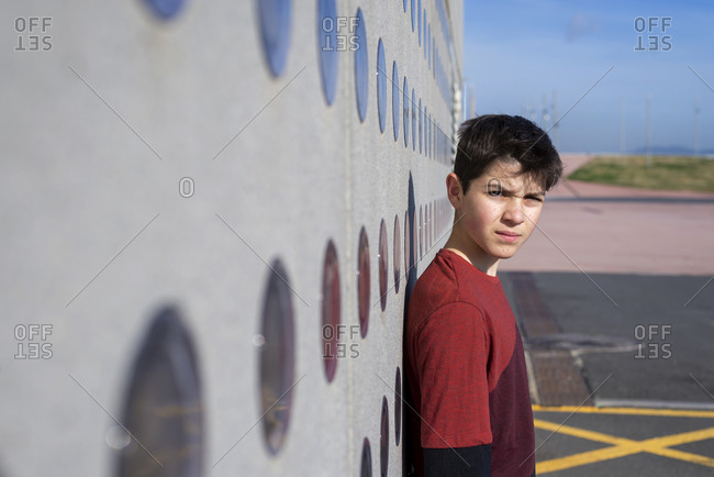 Portrait of cheerful teen leaning on wall while looking camera