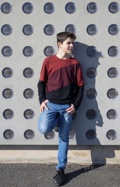 Portrait of cheerful teen leaning on wall while looking away
