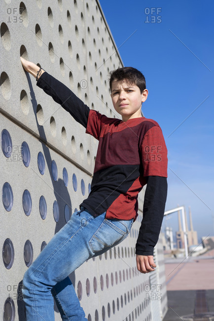 Portrait of a teen hanging up on wall while looking to camera