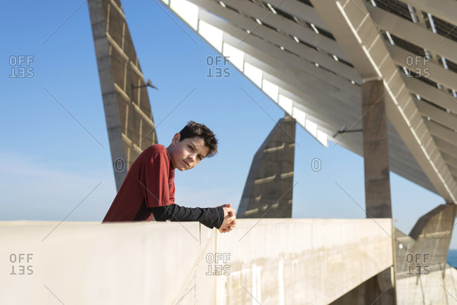 Young cheerful teen leaning on a wall, looking camera in sunny day