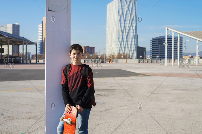 Young teen leaning on a pole holding skate, looking away in the city