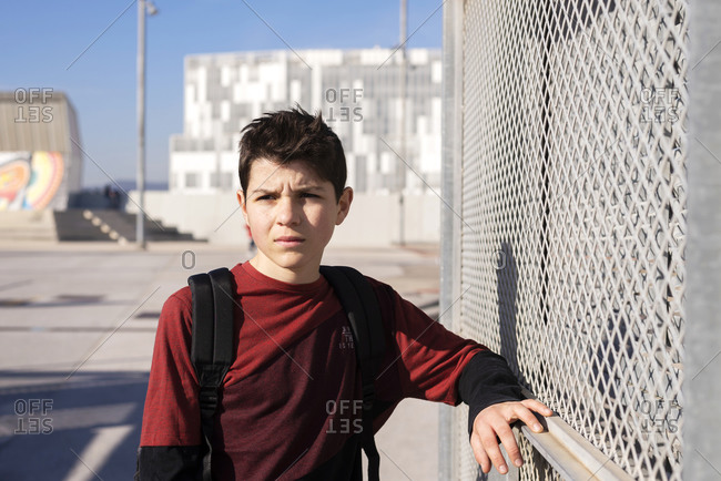 Portrait of cheerful teen leaning on metallic fence while looking away