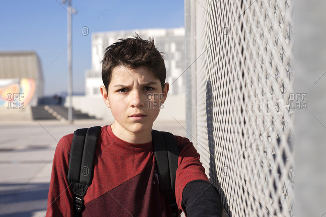 Portrait of cheerful teen leaning on metallic fence, looking camera