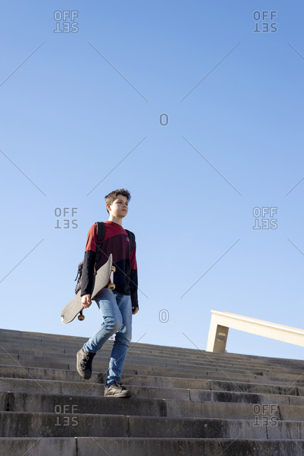 Young teen holding a skateboard going down stairs in a city park