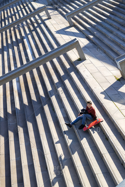 Young teen sitting on stairs outdoors, looking camera in sunny day