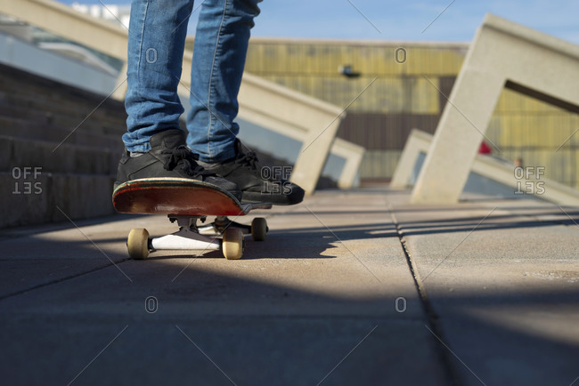 Young boy skateboarding in a city park in sunny day, low angle view