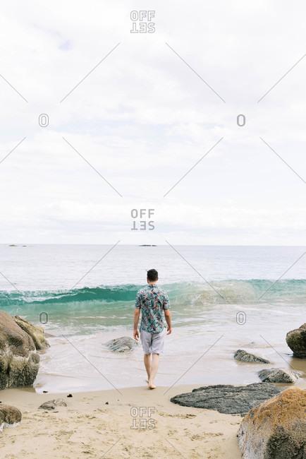 Man walking toward the water on a rocky Massachusetts beach.