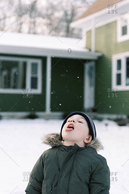 Little boy standing in his front yard trying to catch snow flakes.