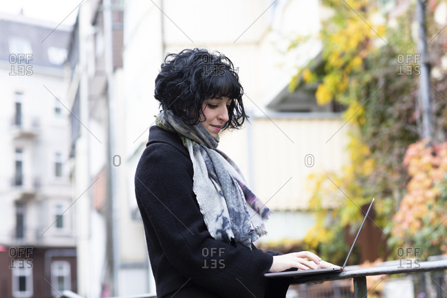 young woman working with laptop outside